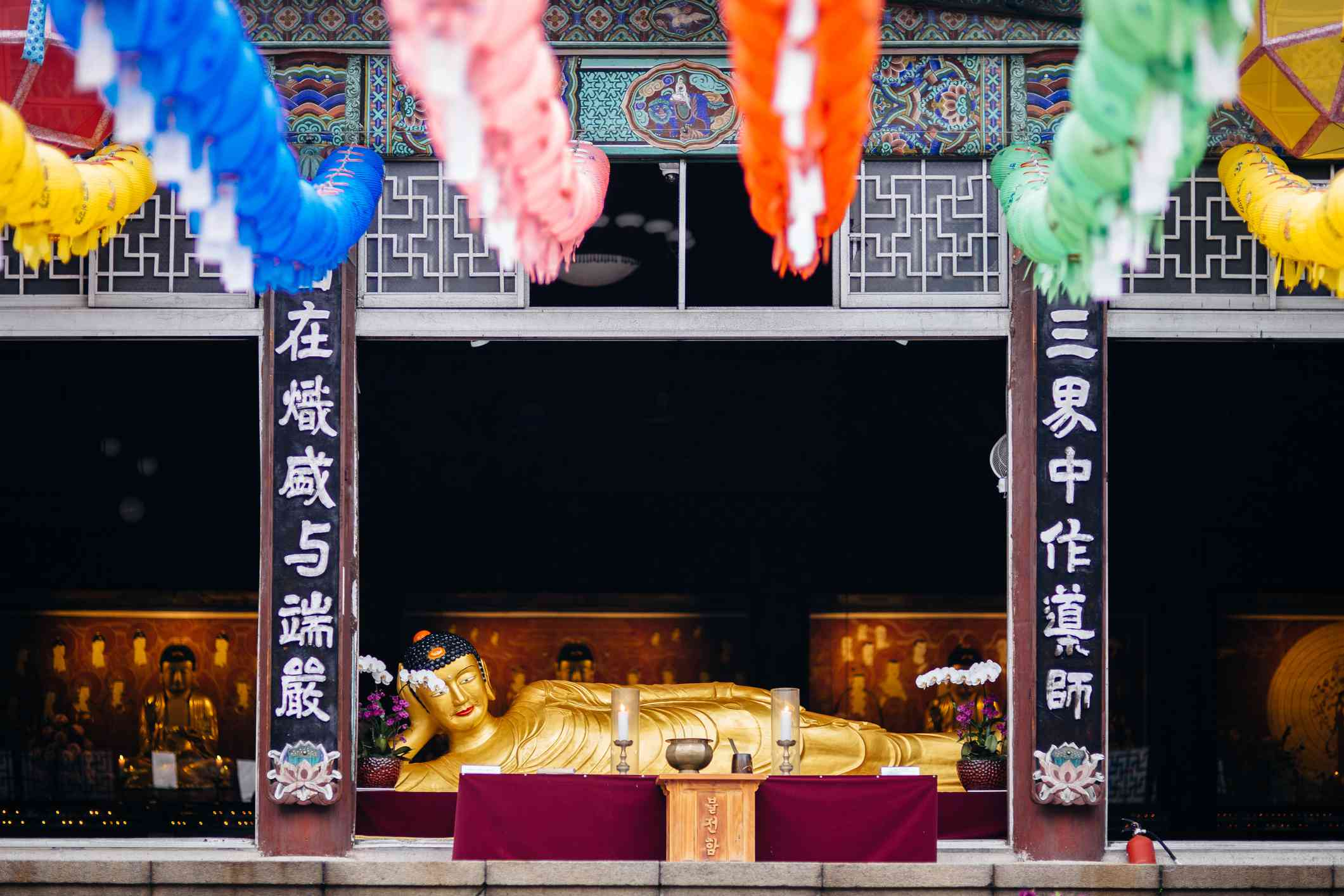 Photograph of golden reclining Buddha statue with colorful lanterns in the foreground
