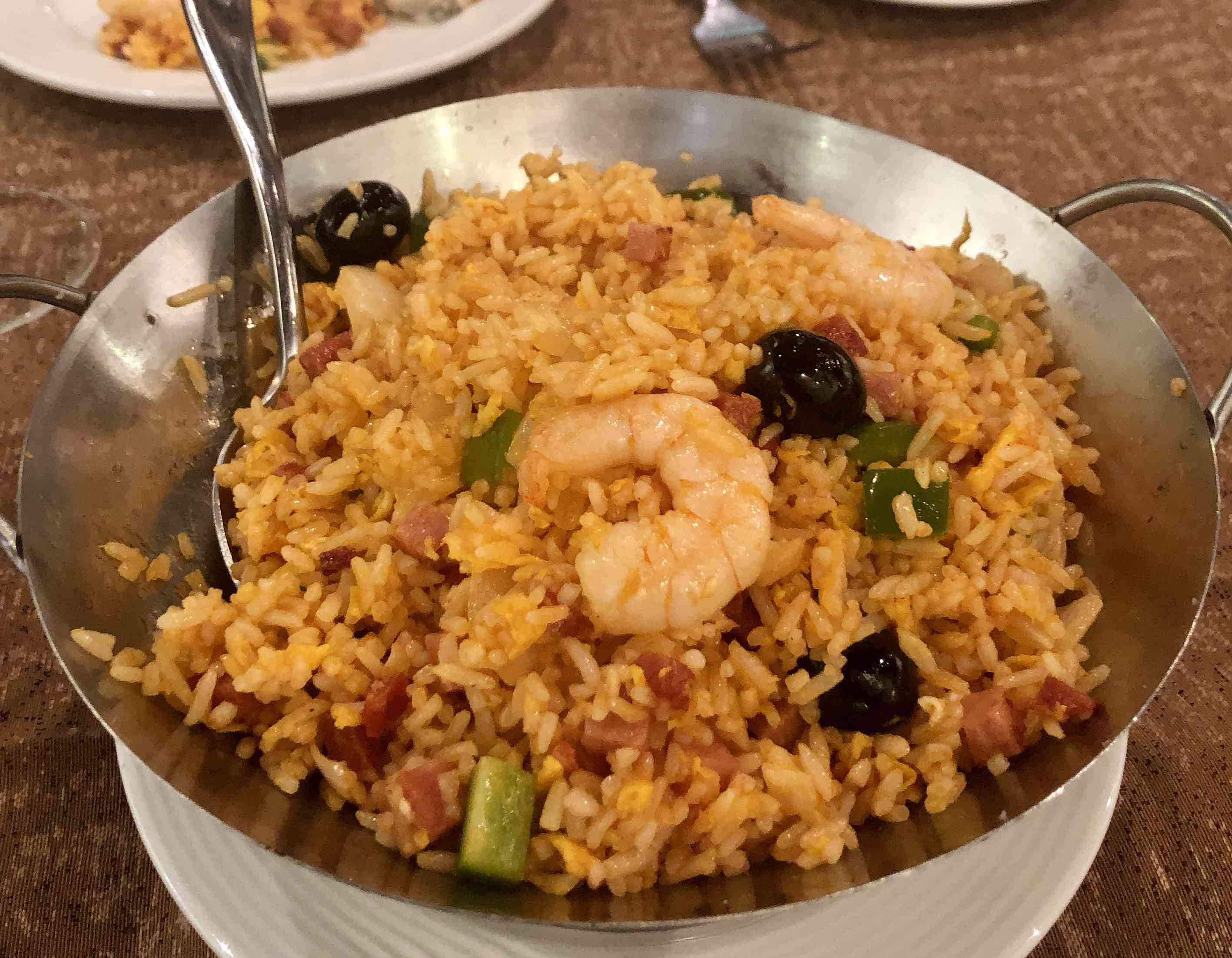 Portuguese fried rice with shrimp and olives in a metal bowl