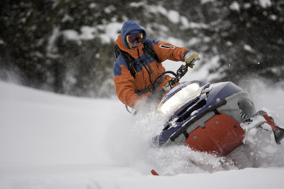 Guy on a snowmobile taking a powder turn