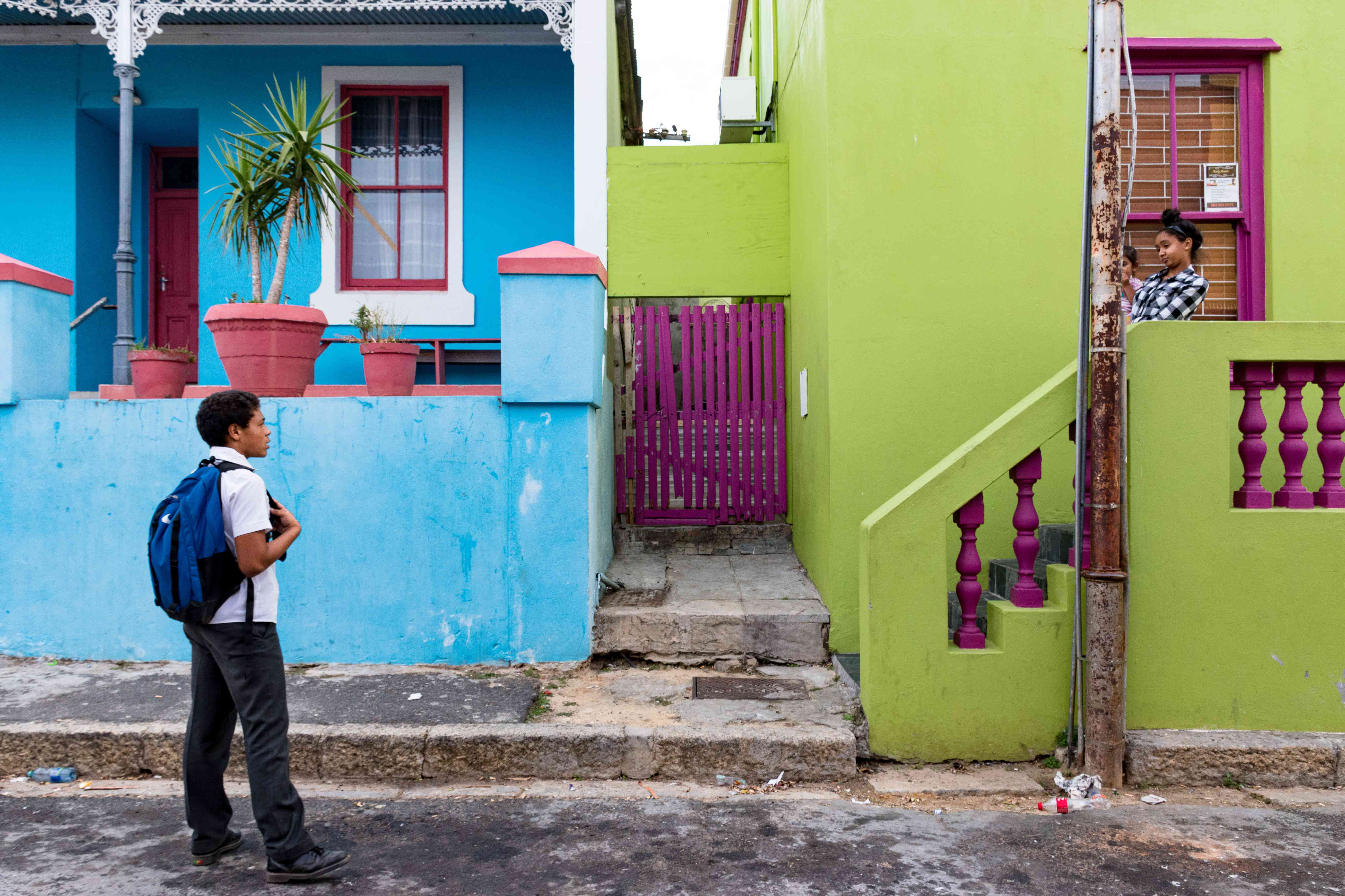 Two people talking infront of very colorful houses