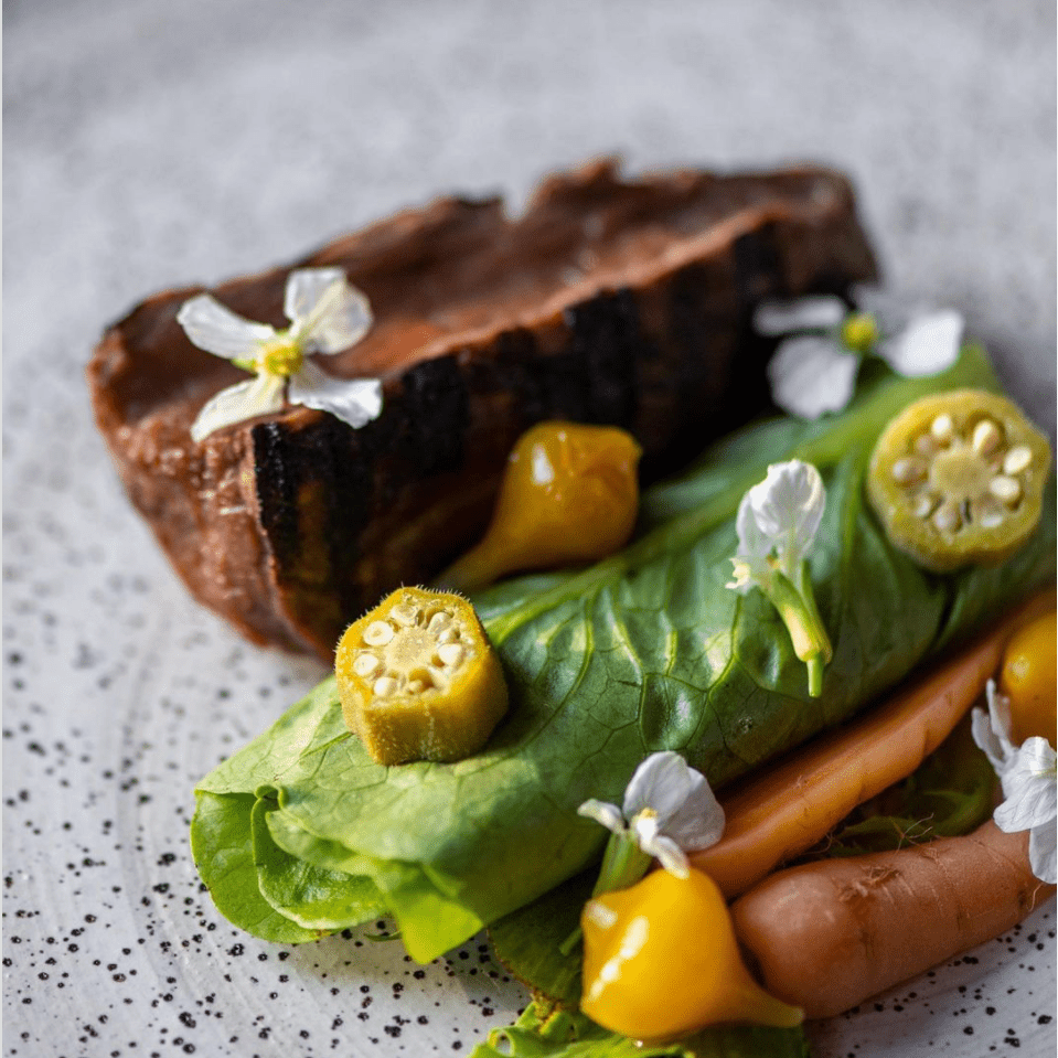 closeup of steak and vegetable dish garnished with flowers