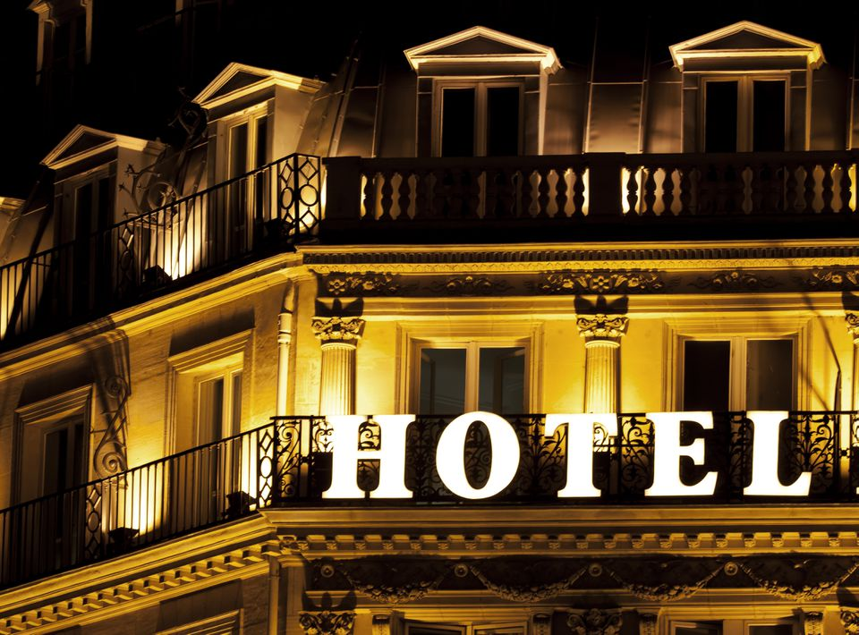 Brightly lit HOTEL sign on a hotel balcony in France