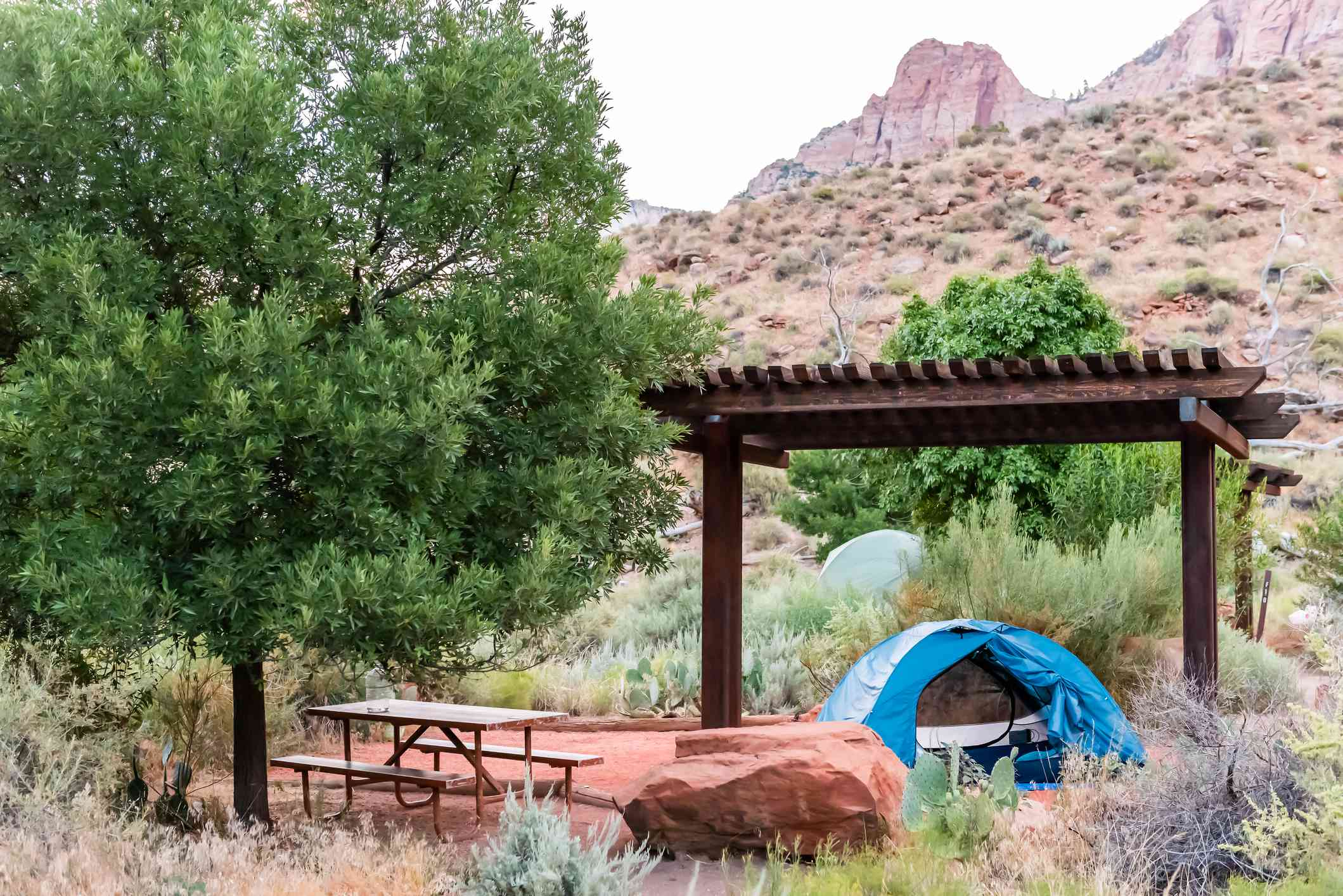 Zion National Park in Utah morning with tent on camp site at Watchman Campground with picnic table and pergola cover
