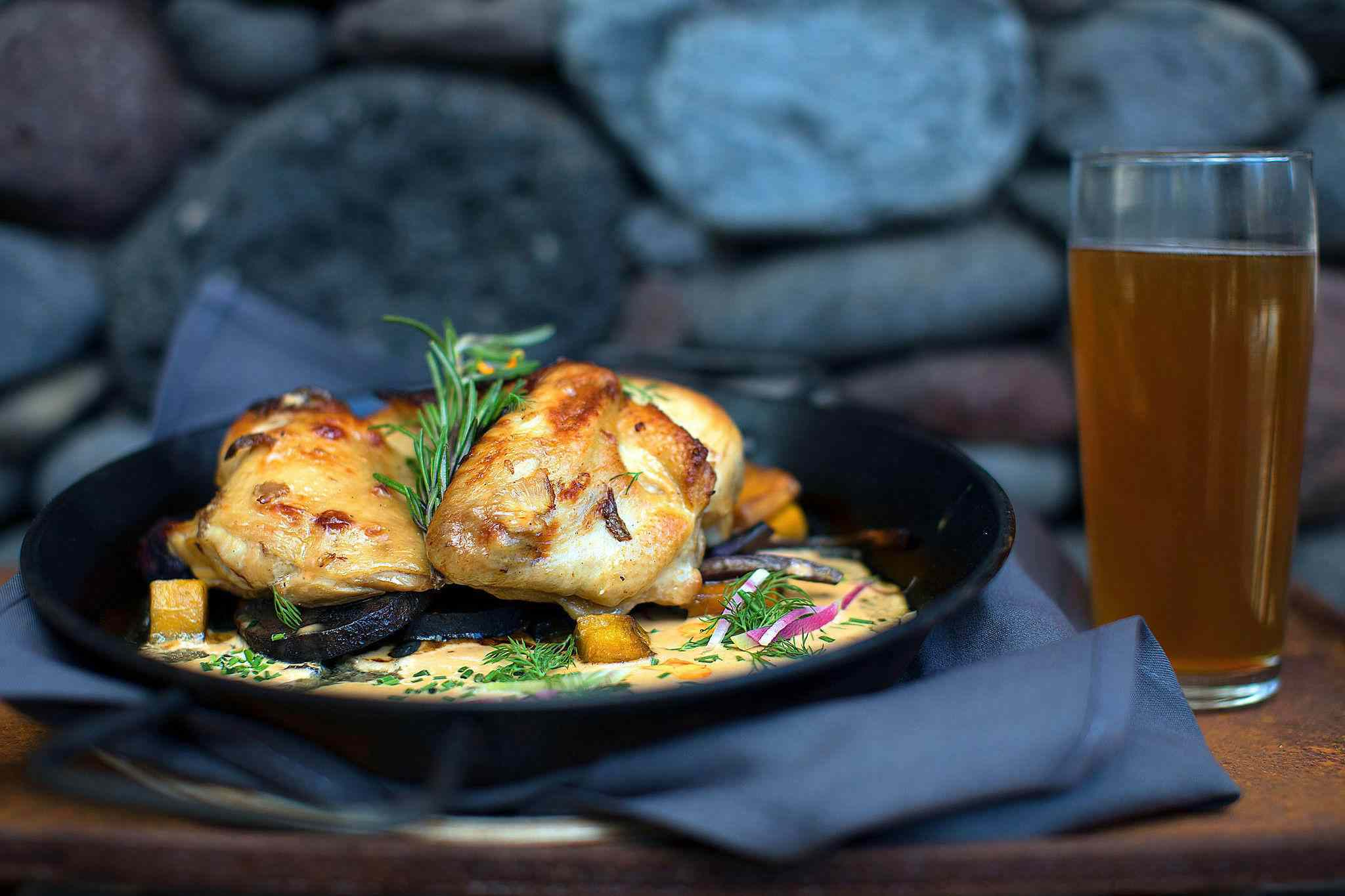 Roasted half-chicken with a dijon glaze garnished with rosemary on a black plate with a glass of beer