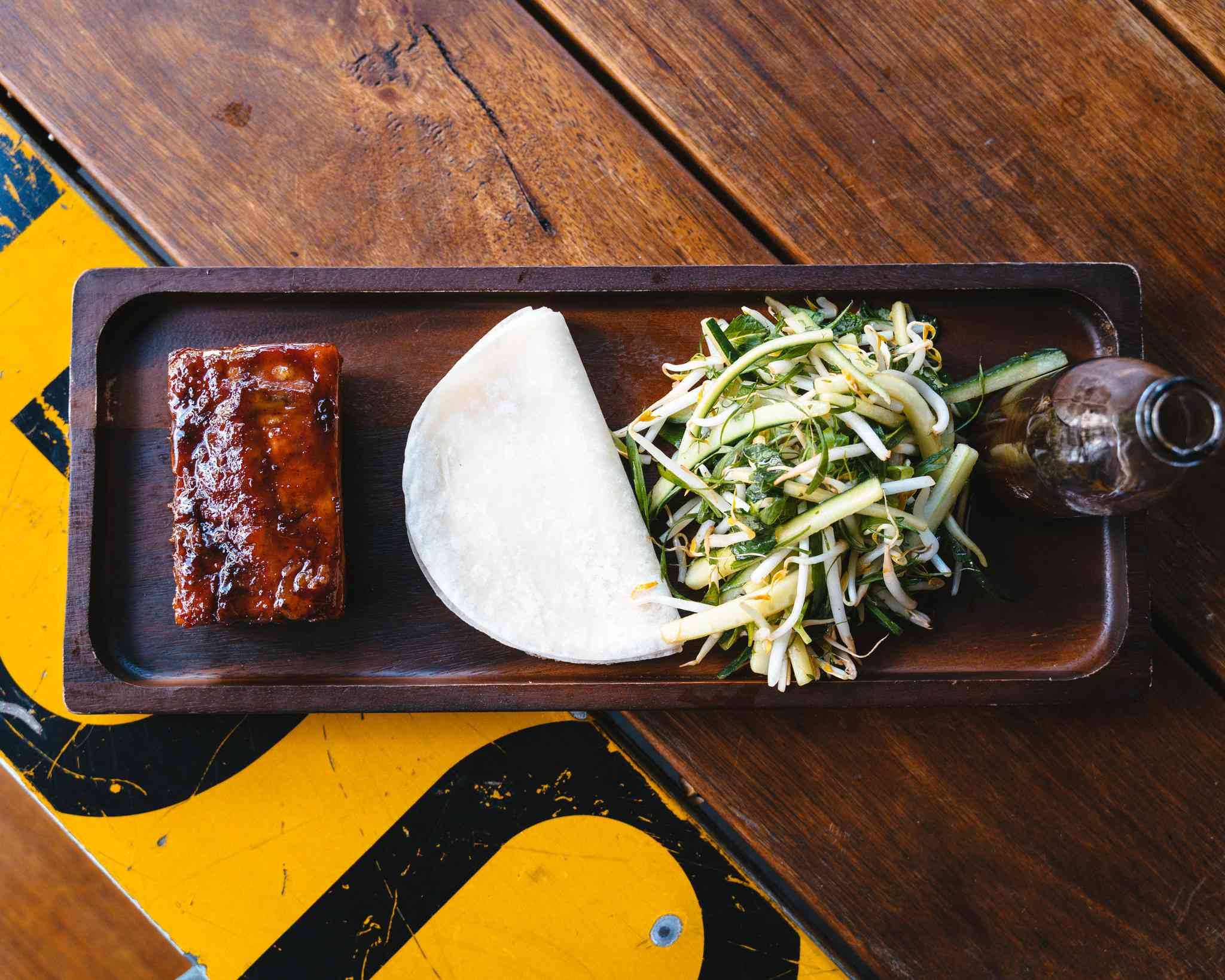 Aerial shot of pork belly with bean sprouts and pancakes on wooden board