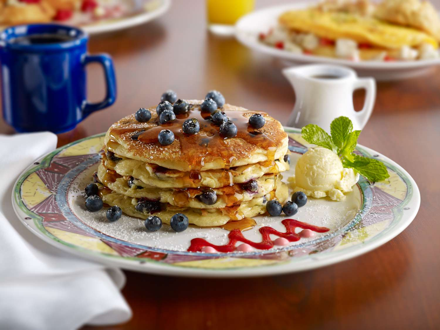 stack of four blueberry pancakes on a colorful plater with blueberries and syrup drizzled on top and butter on the side