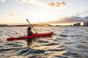 girl kayaking in front of a modern Downtown Cityscape during a dramatic sunset. Taken in Miami, Florida,