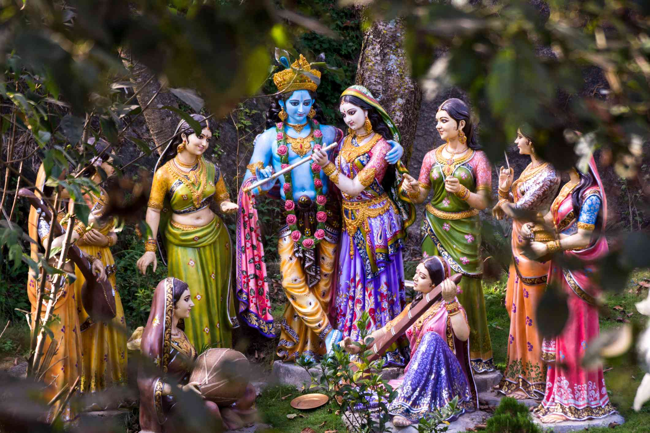 blue Lord Krishna figurine surrounded by figurines of female characters wearing saris