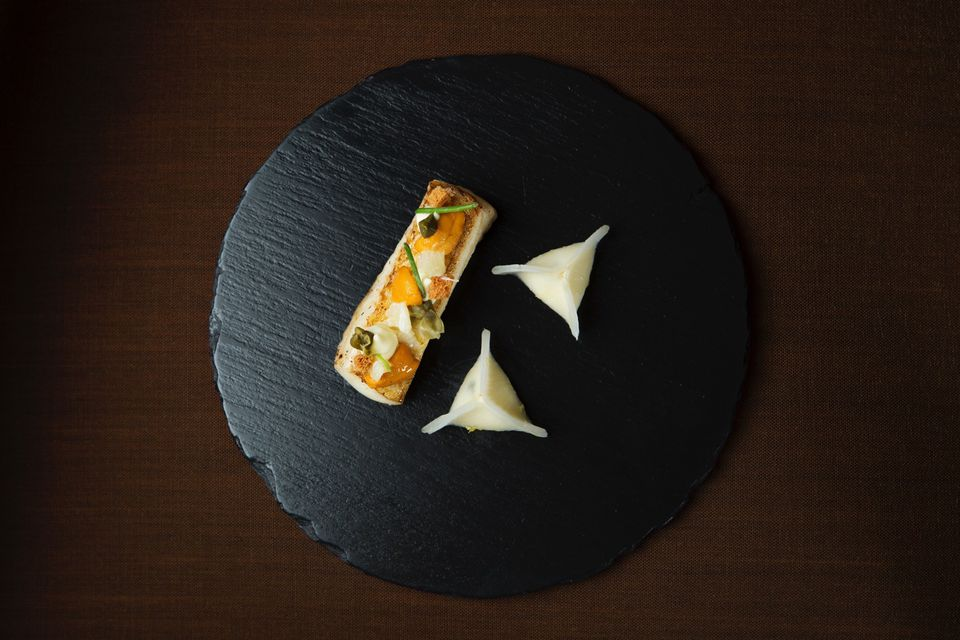 Artfully plated halibut on a black plate from TRB Forbidden city
