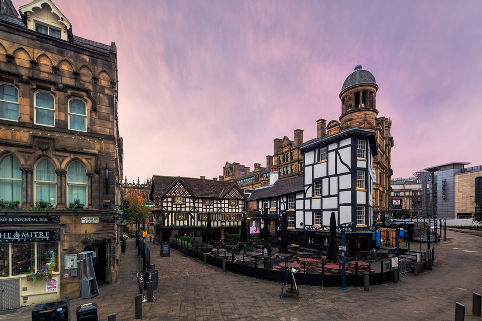 Pastel skies over the historical architecture of Shambles Square in the middle of the city of Manchester, UK.