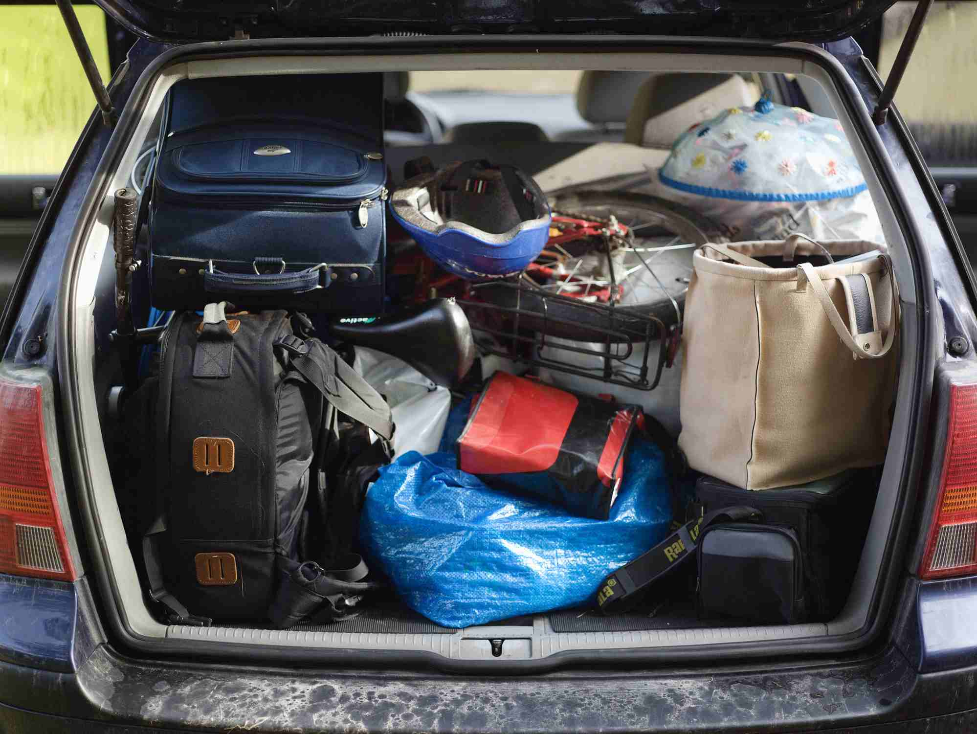 A car with a fully packed trunk full of suitcases.