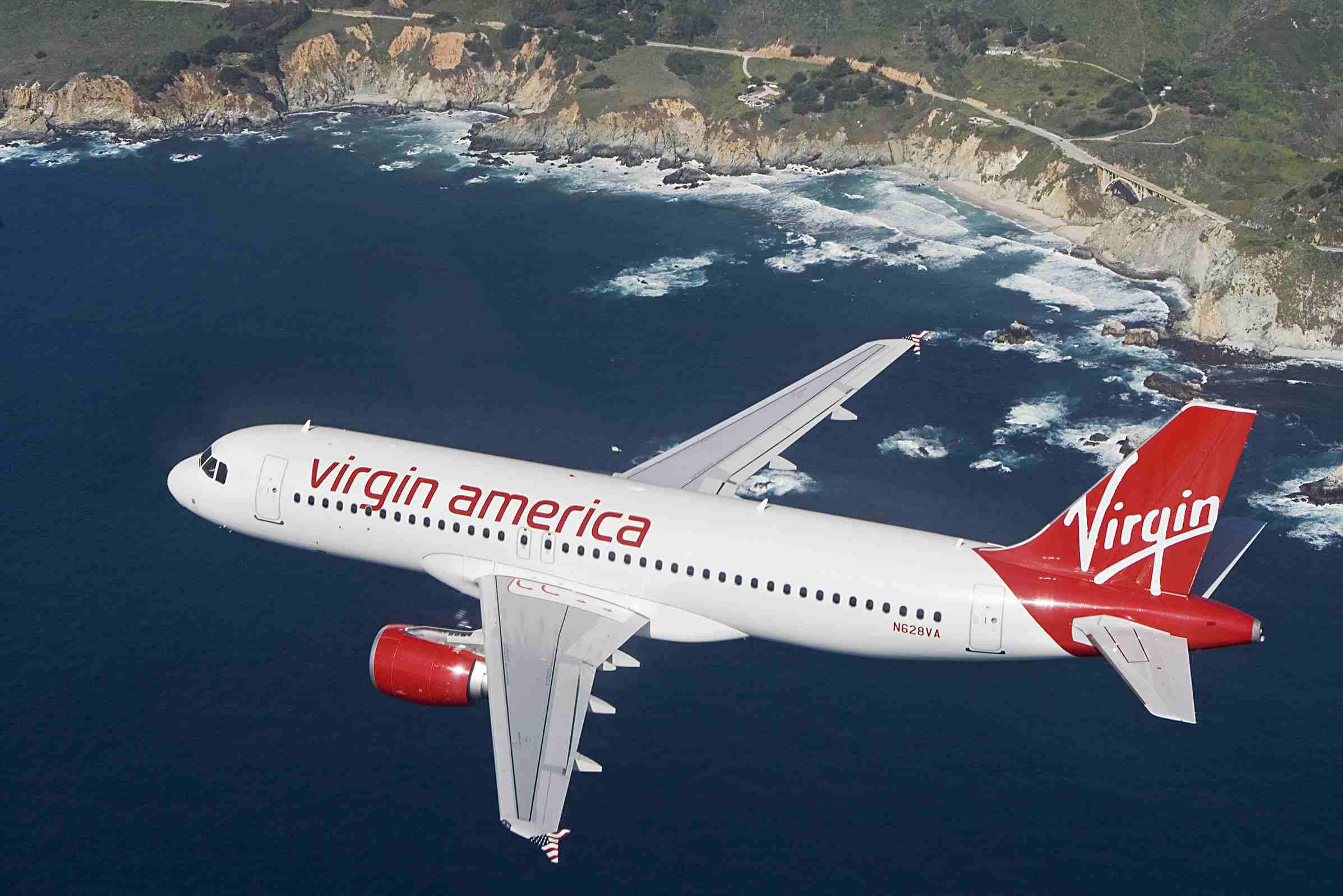 Virgin America flying over a coastine