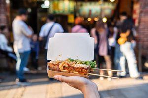 Young woman traveler walking holding stinky Tofu at a Taiwanese food street