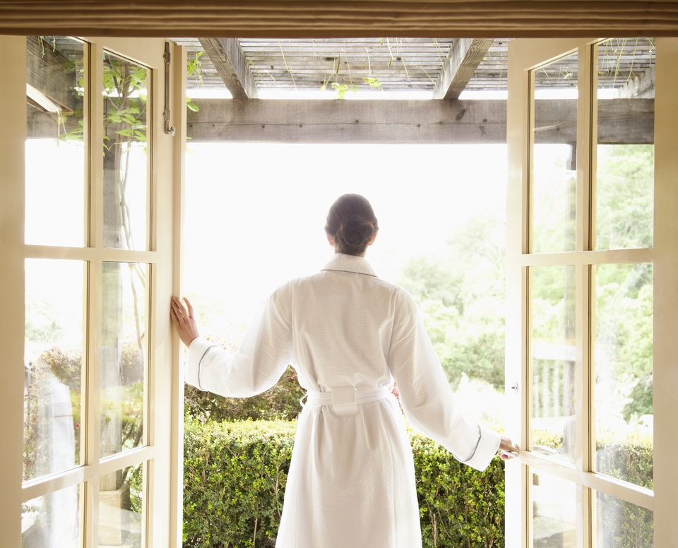 Woman in bathrobe walking out of a luxury spa overlooking wine country in California