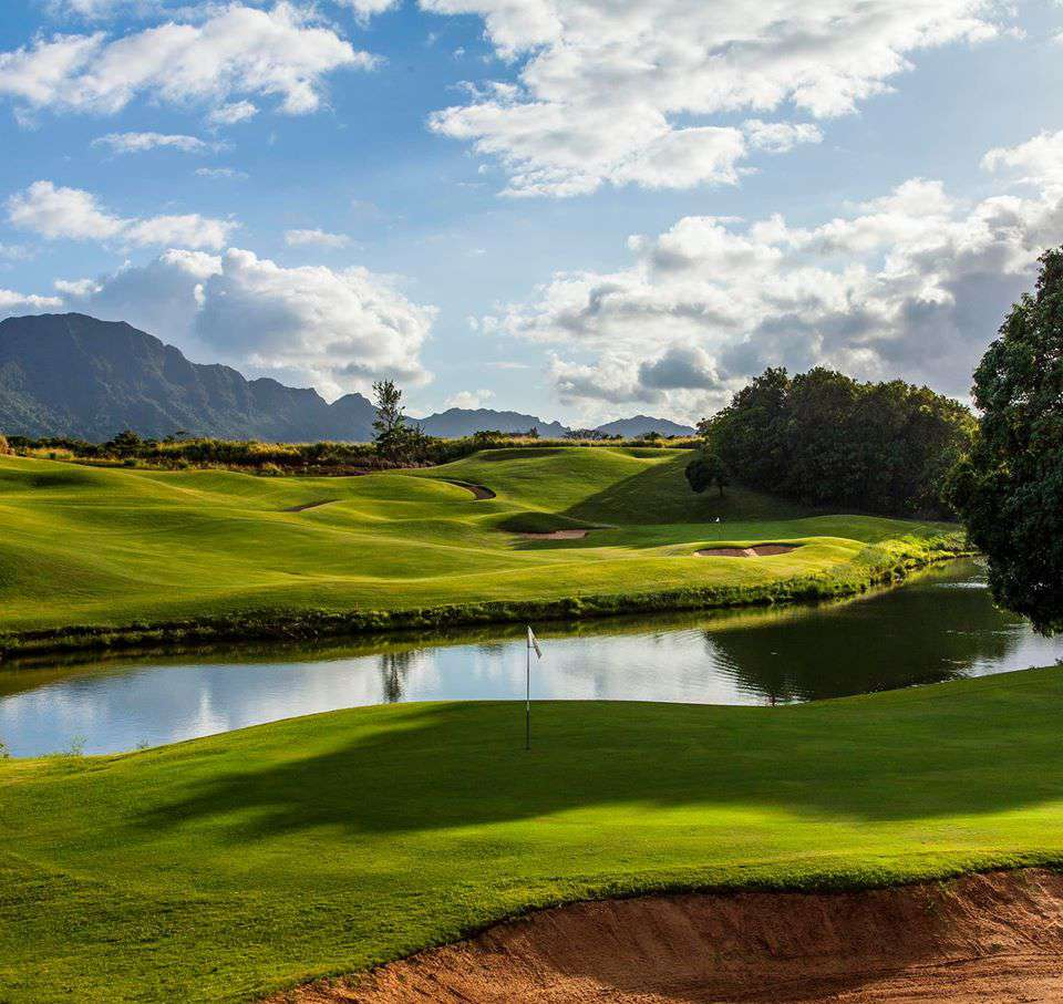 golf course with sand trap and water hazard and mountains in the background