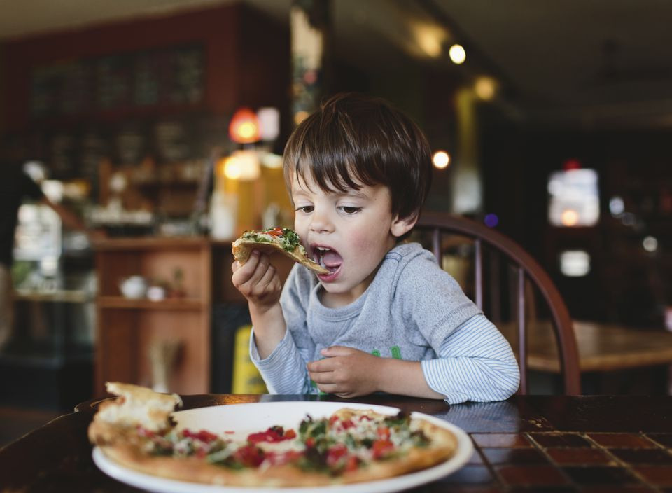 Young Boy Eating Pizza In A Restaurant