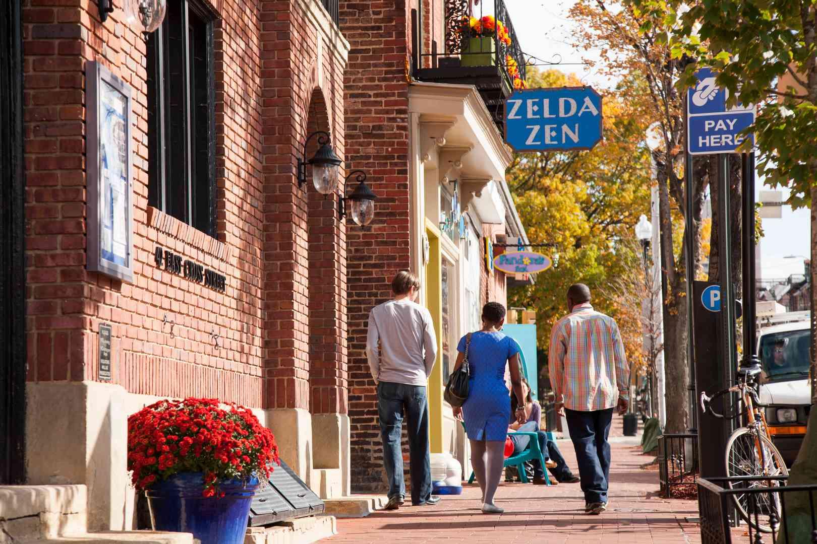 Un hombre negro, una mujer negra y un hombre blanco caminando por una calle con edificios de ladrillo rojo en Baltimore