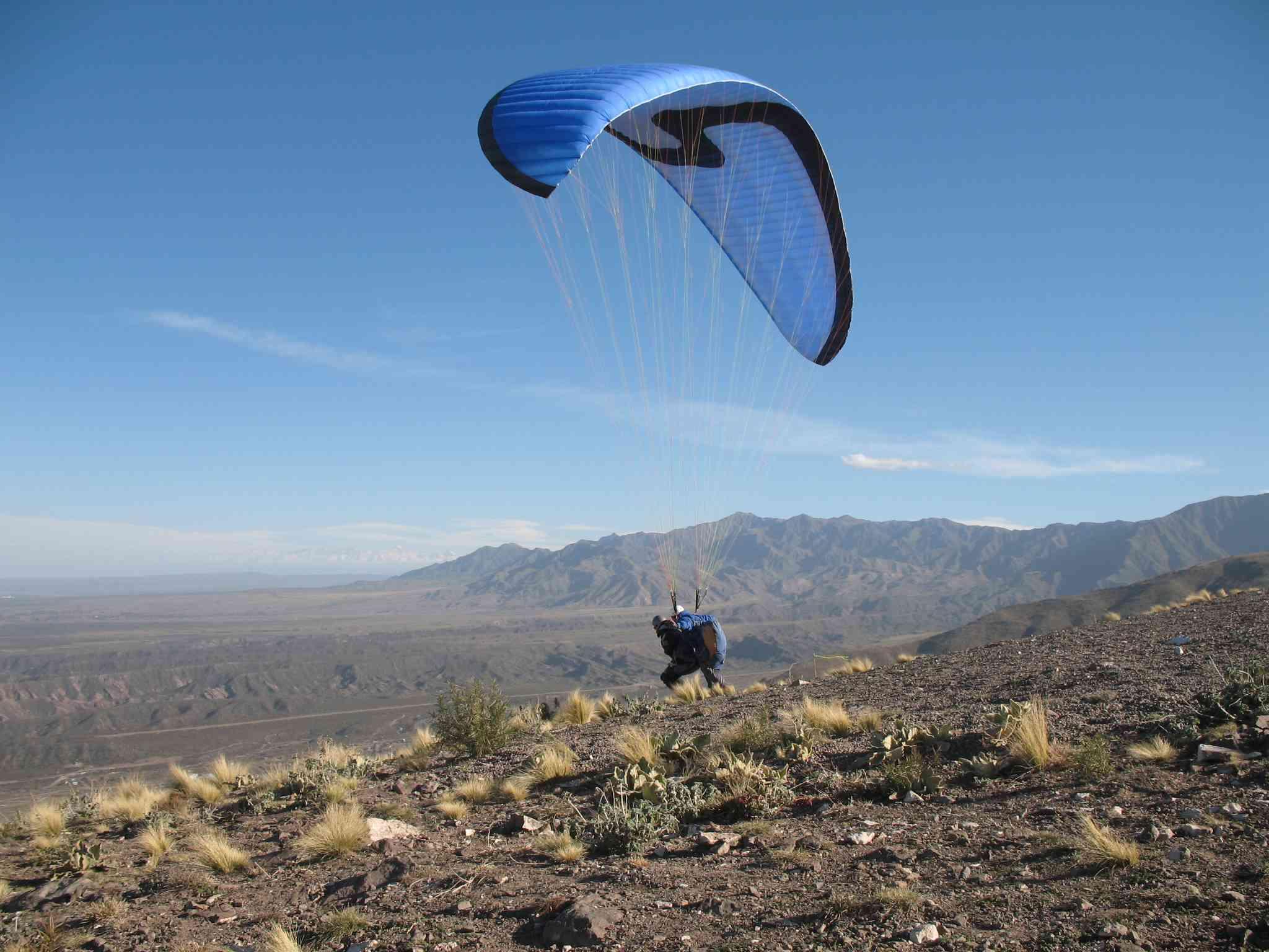 brown mountain landscape with blue paraglider landing