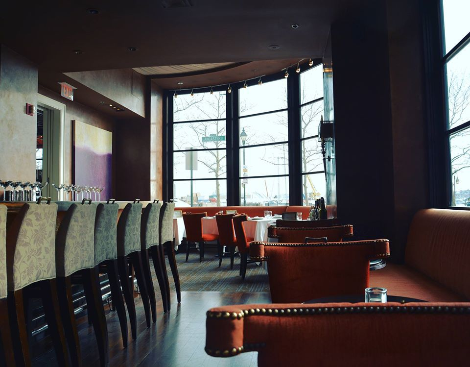 Orand studden couches and wing back chairs in a restaurants with large windows
