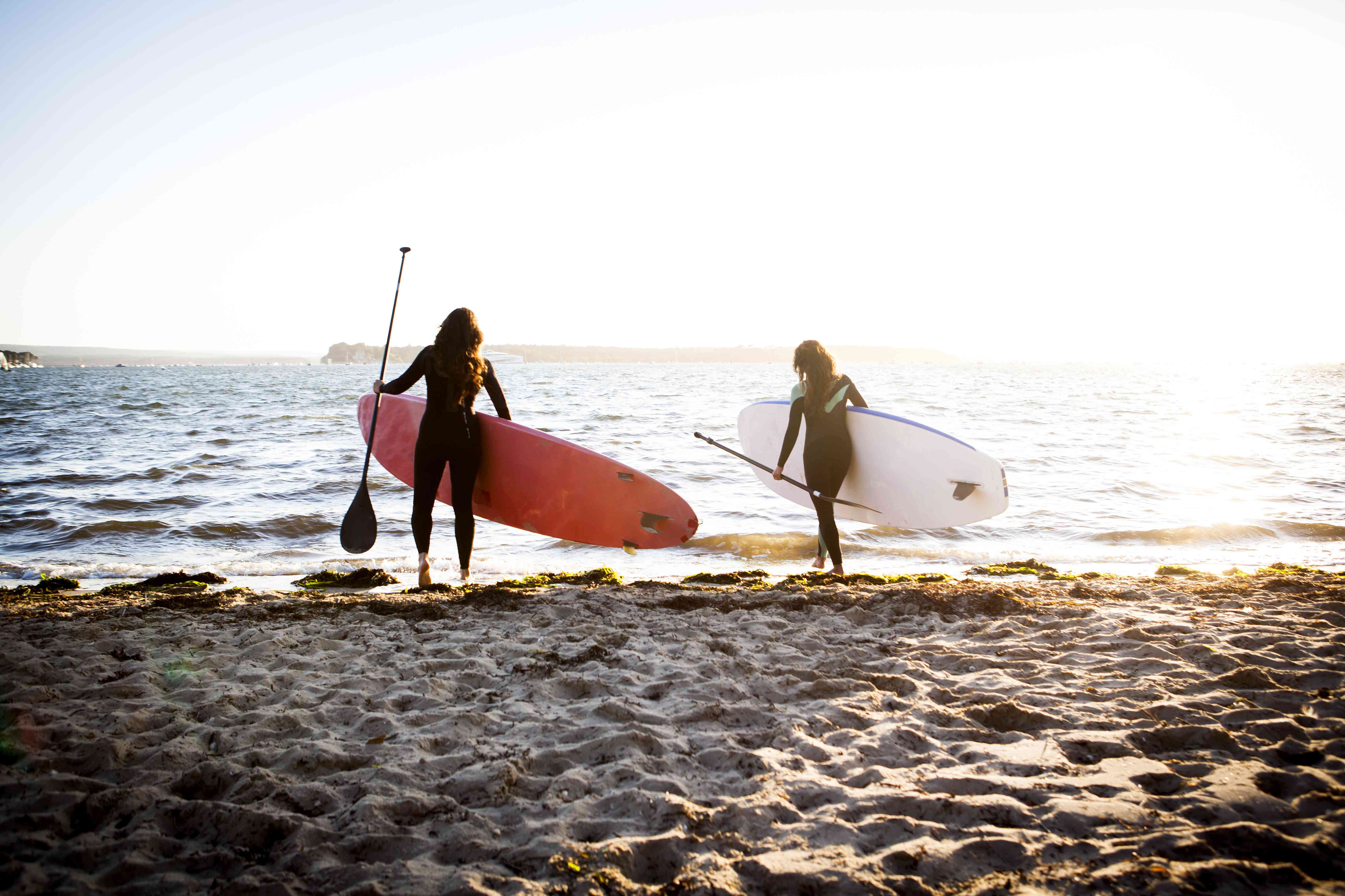 mid aged woman and teenage daughter paddle board