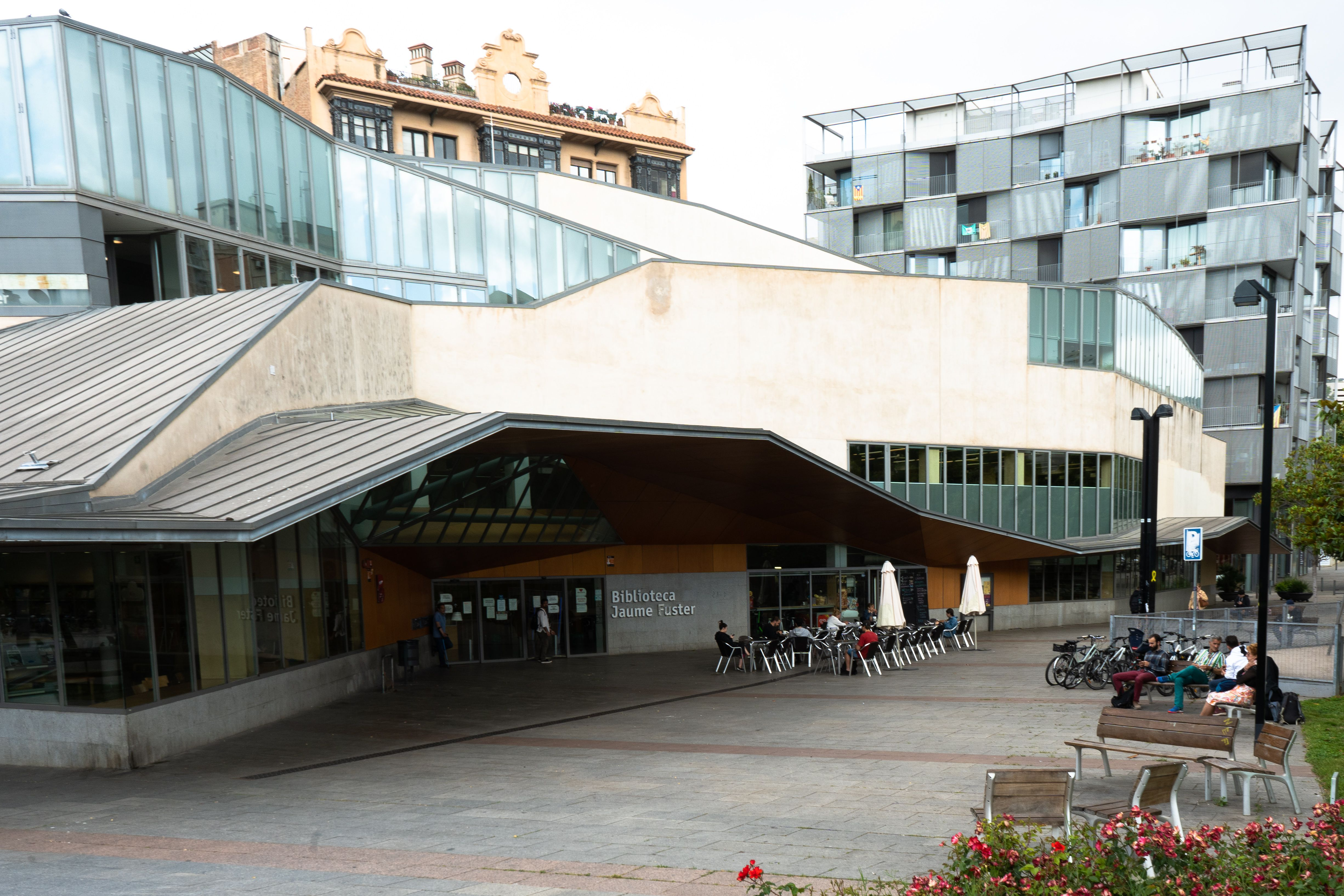 The exterior of the Jaume Fuster library with people sitting at tables