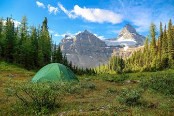 a tent on a field in the Rocky Mountains