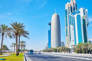 : The palms of Sheraton park stretch along the automobile road in Corniche street, separating coastal promenade and skyscrapers of West Bay neighborhood in Doha