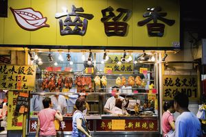 People Walking By Street Food Stand, Meat And Poultry In The Mong Kok Market, Kowloon. Hong Kong; Kowloon, Hong Kong.