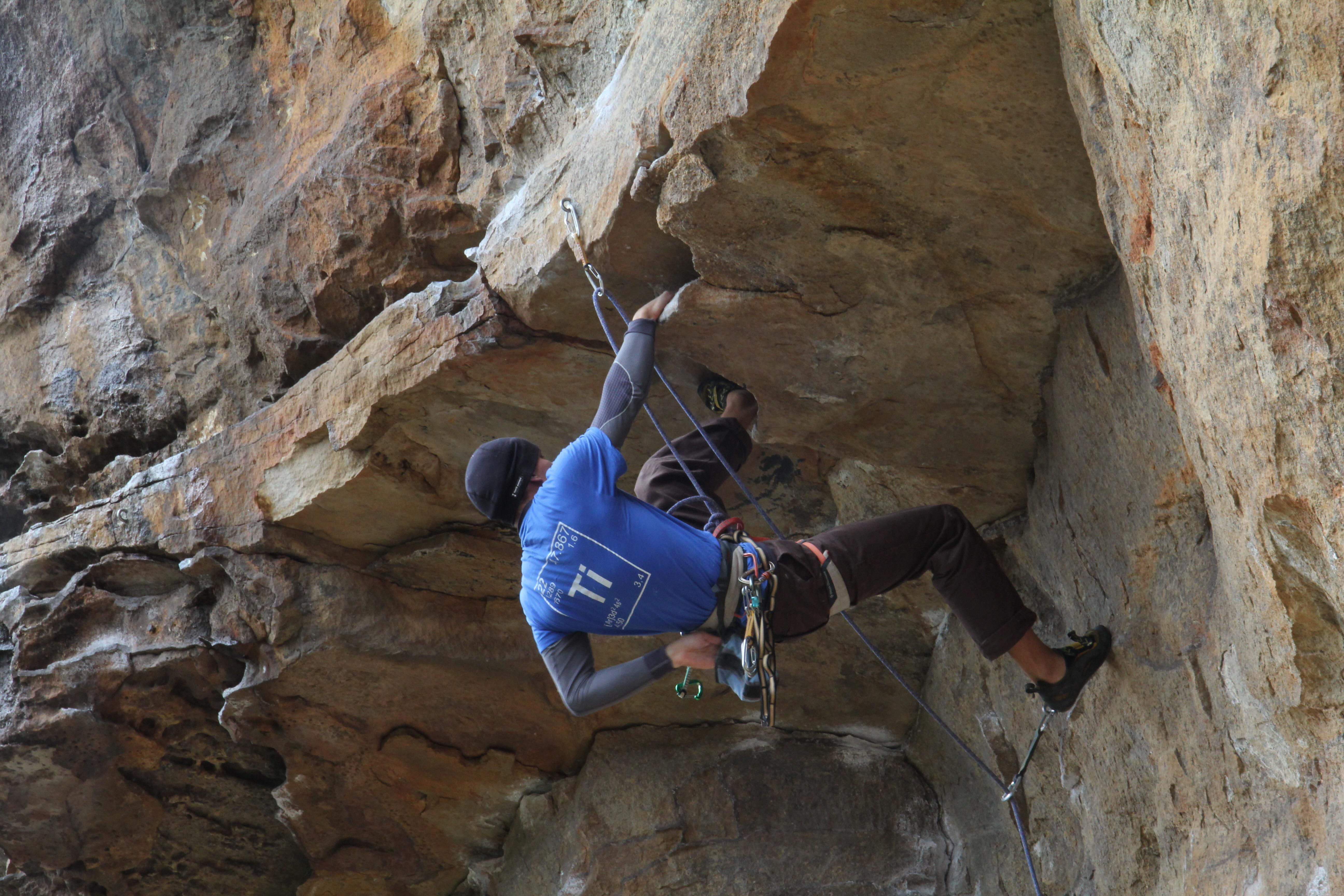 Person with periodic table shirt on while rock climbing.