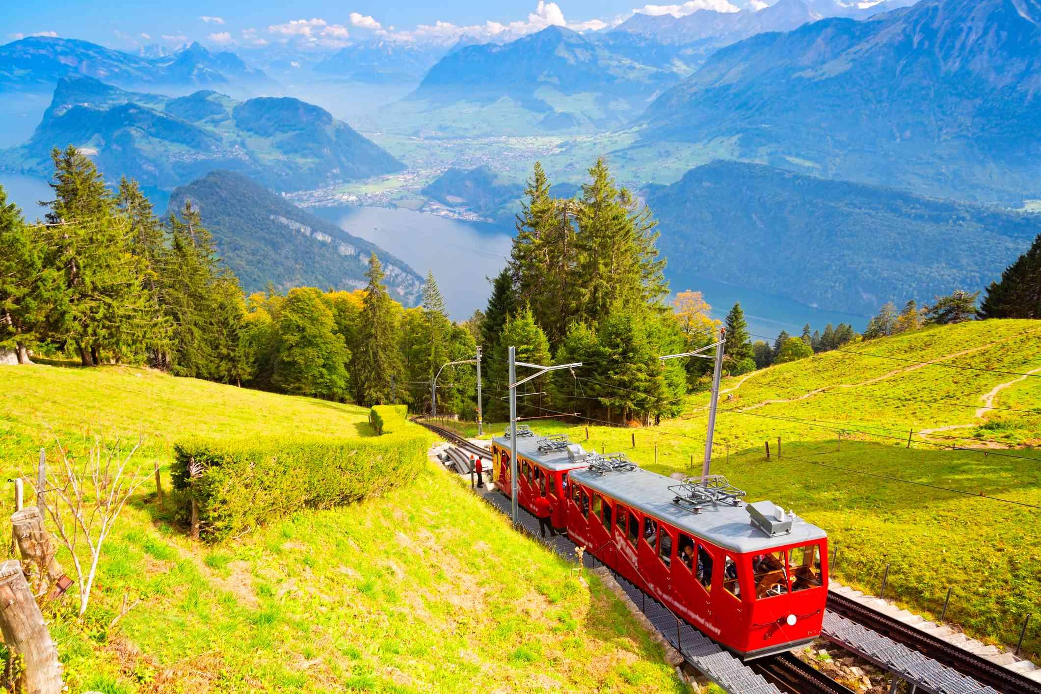 Bright red cogwheel train climbs up Mount Pilatus