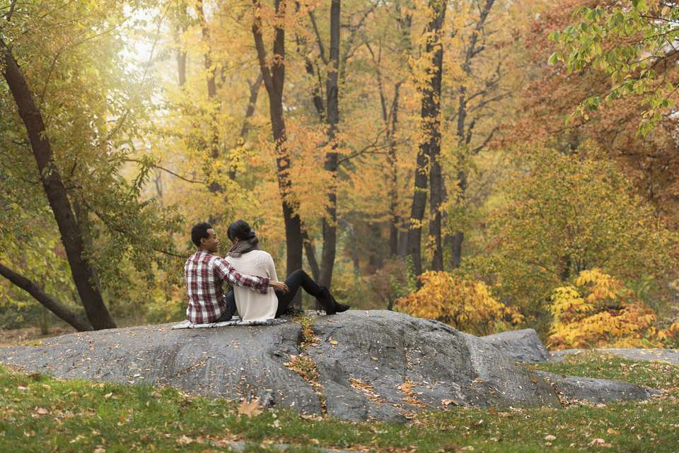 Couple hugging on rock in park