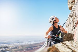 Female rock climber holding rope, looking up