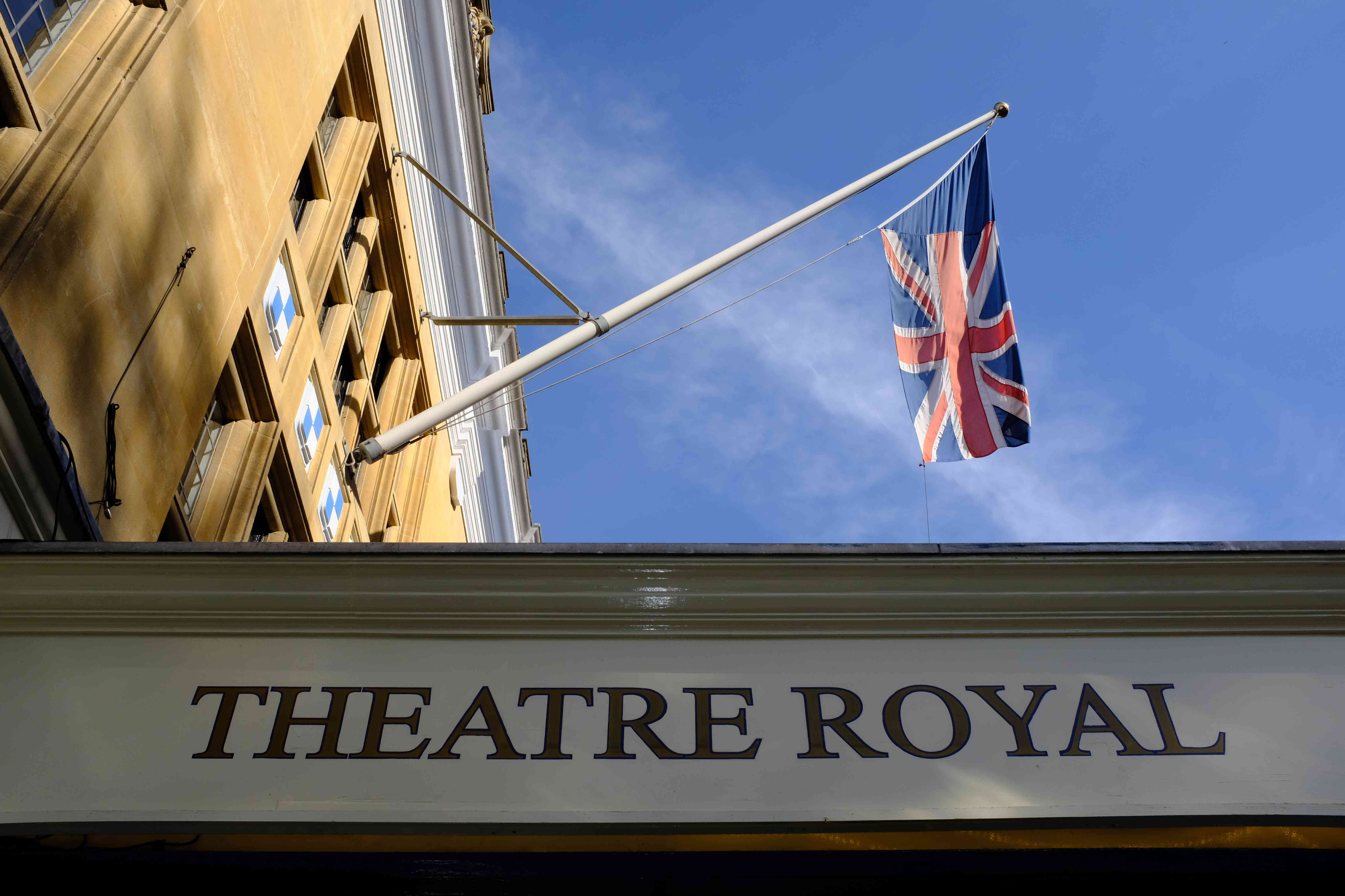 Detail of the exterior of the Theatre Royal Windsor, with its entrance canopy and flagpole with the Union Jack flag, in Windsor, England, on a bright autumn afternoon