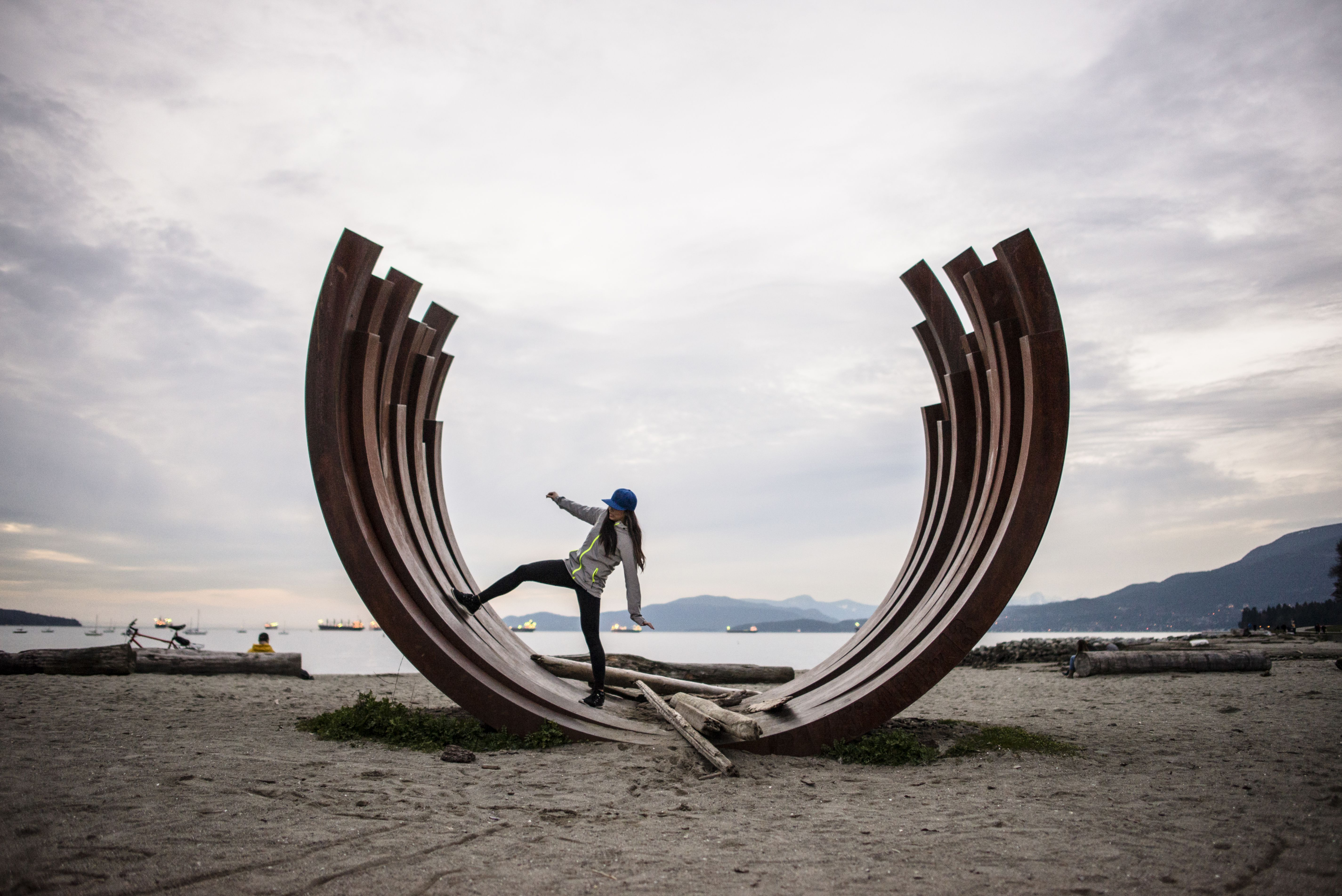 Young woman standing on arc sculpture, English bay, Vancouver, Canada