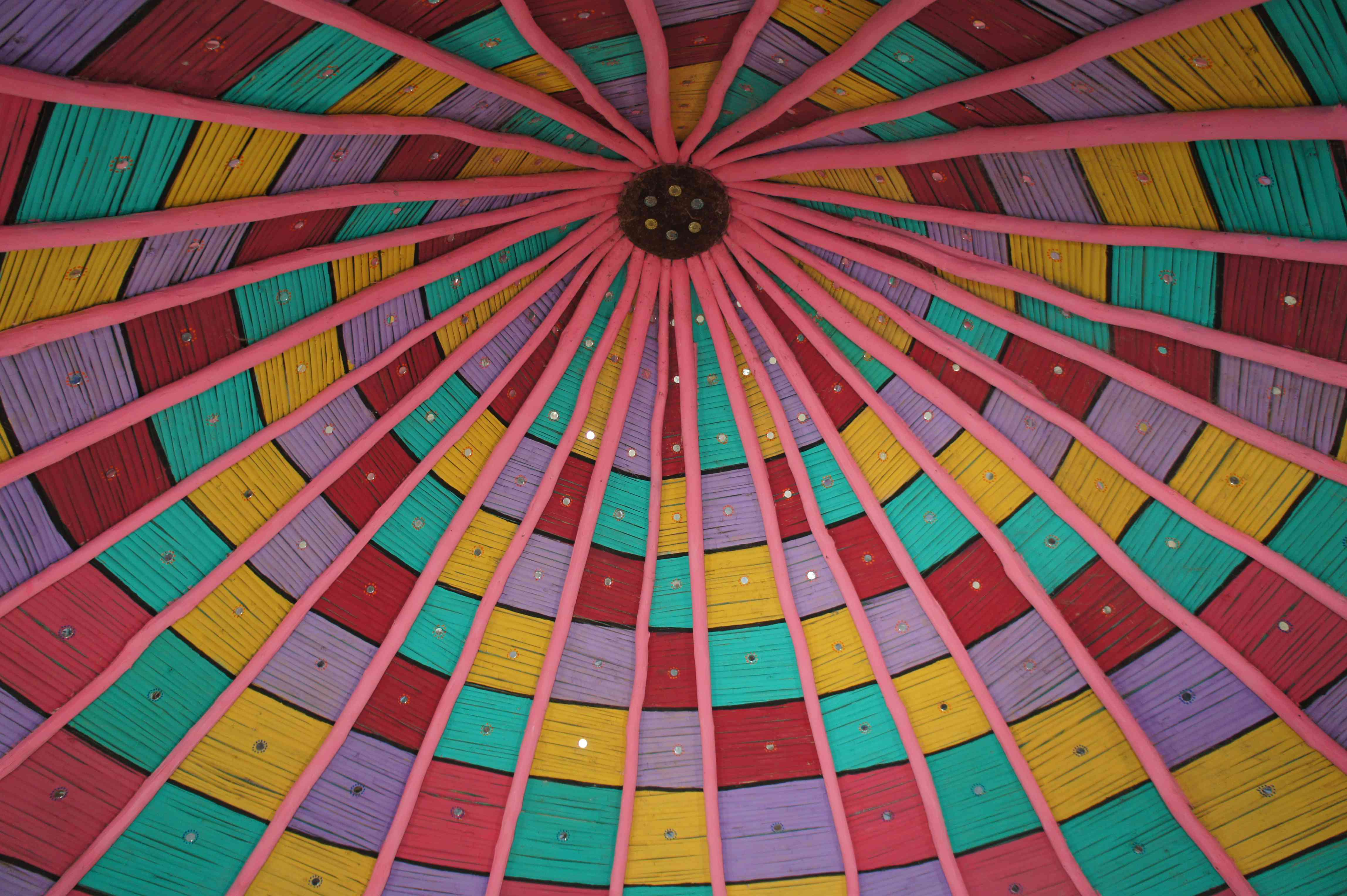 colorful hut ceiling with teal, red, yellow, and purple squares and pink support beams. Each square hass a small round mirror in ir