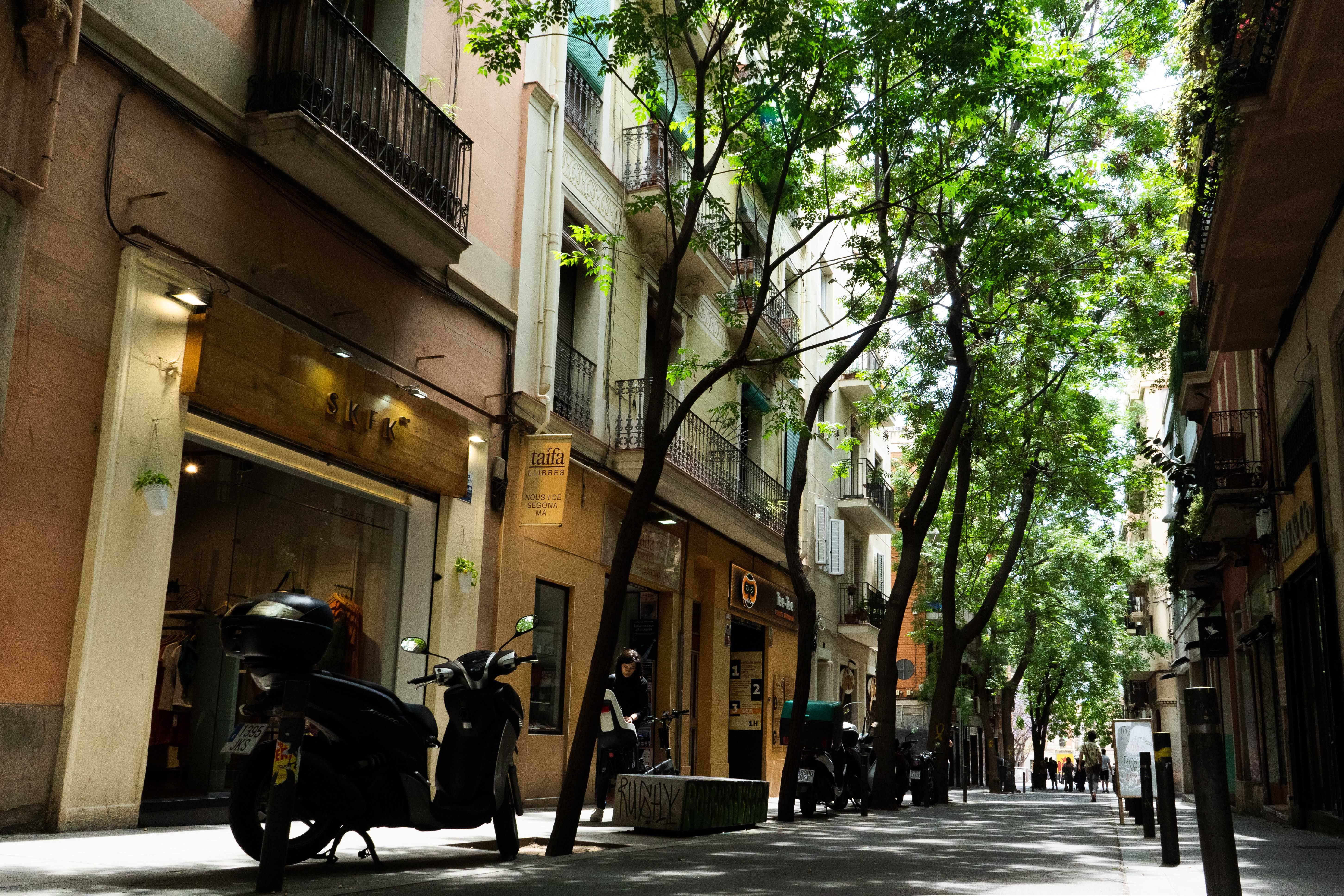 Carrer Verdi a store lined street with trees and bikes parked