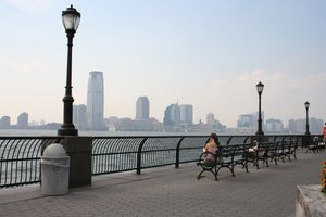 woman sitting on a bench in battery park, nyc