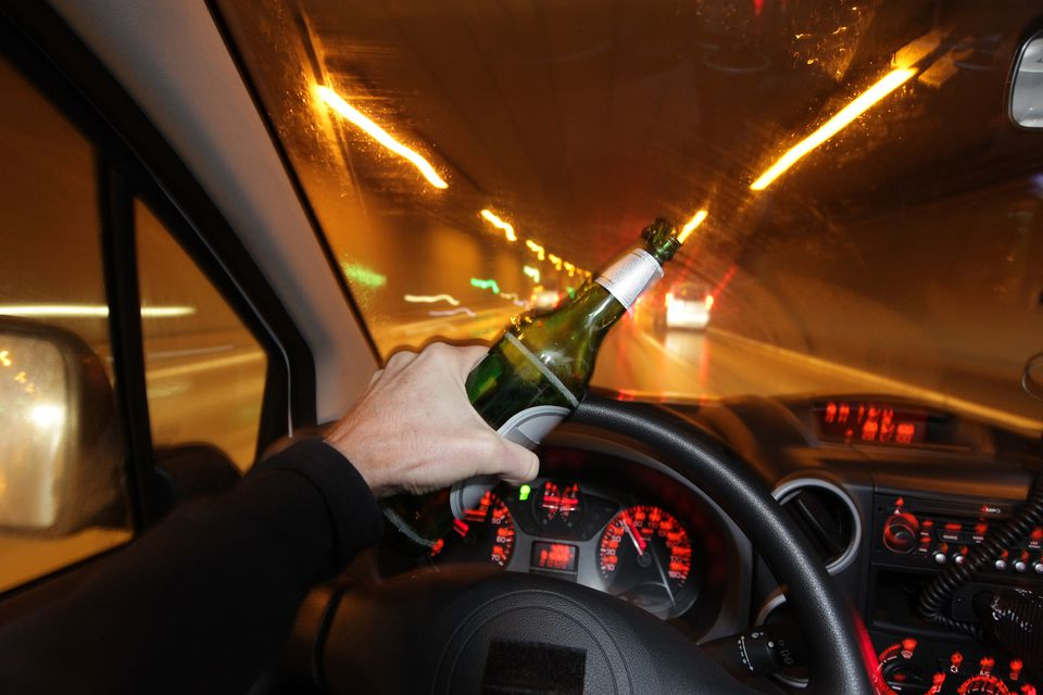 A car driver is drinking beer while he is driving through a tunnel