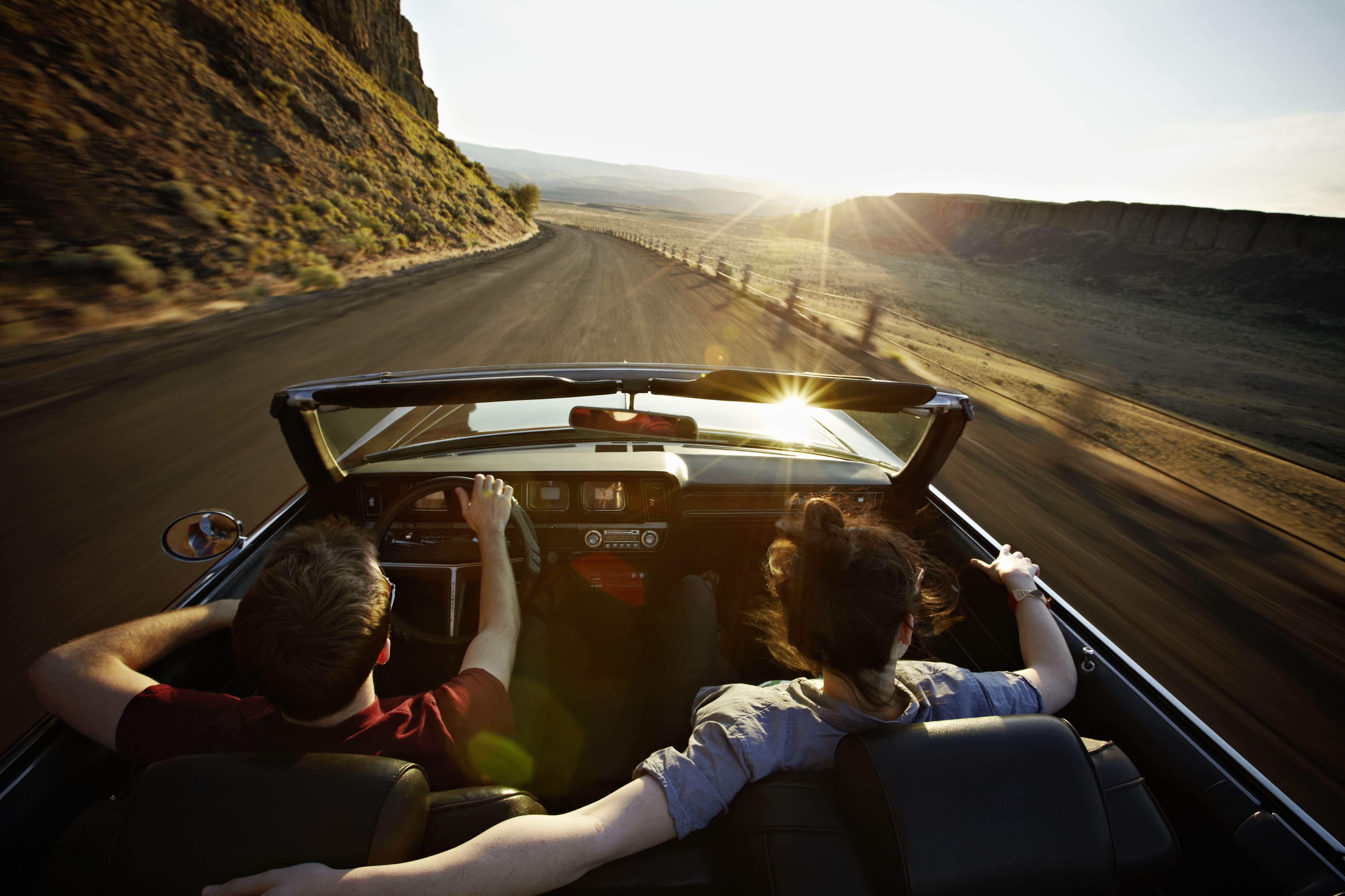 Pareja joven conduciendo un descapotable en puesta de sol