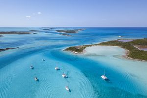 White boats float in the blue waters off the Exumas in the Bahamas