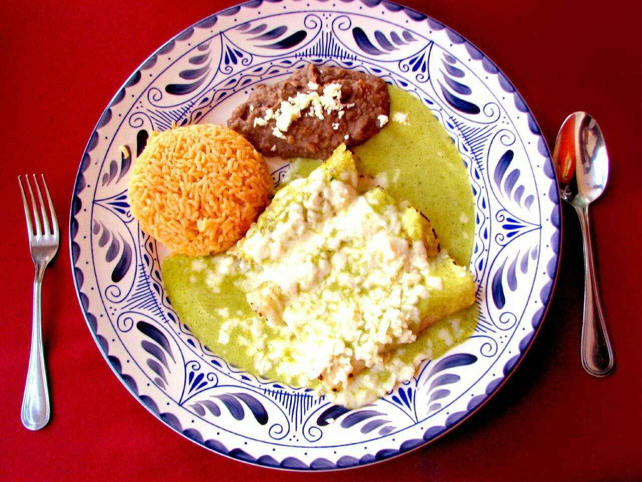 Chicken Enchiladas With Rice And Beans Served In Plate