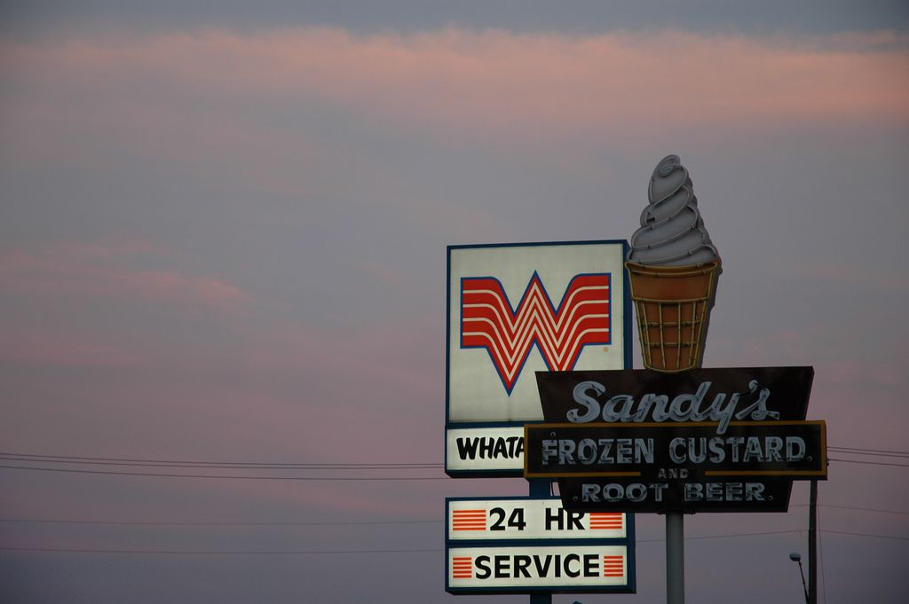 The Sandy's Hamburgers sign in front of a Whataburger sign