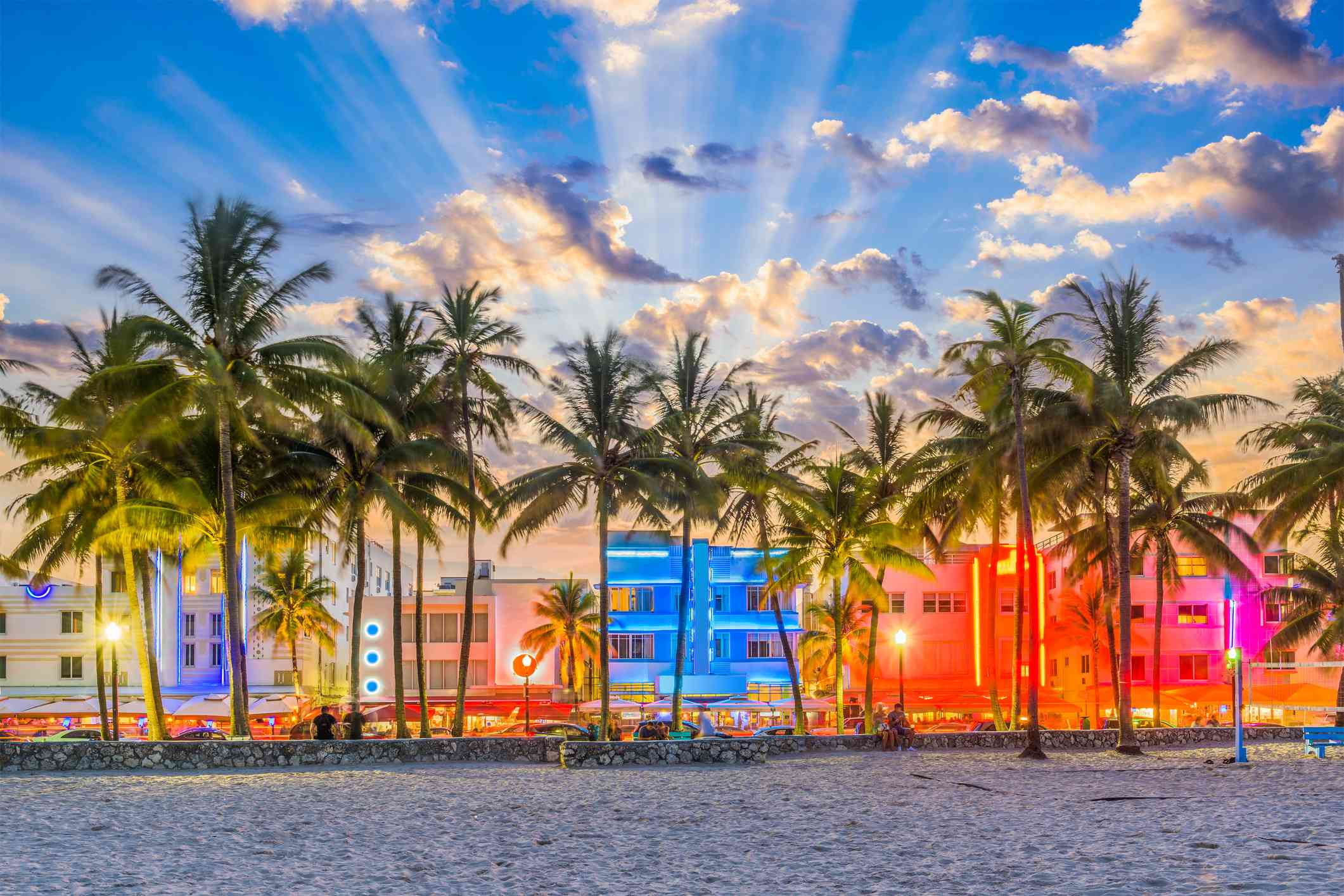 row of buildings on a waterfront with neon decorations. there are palm trees in front of the buldings and shafts of light illuminating the sky