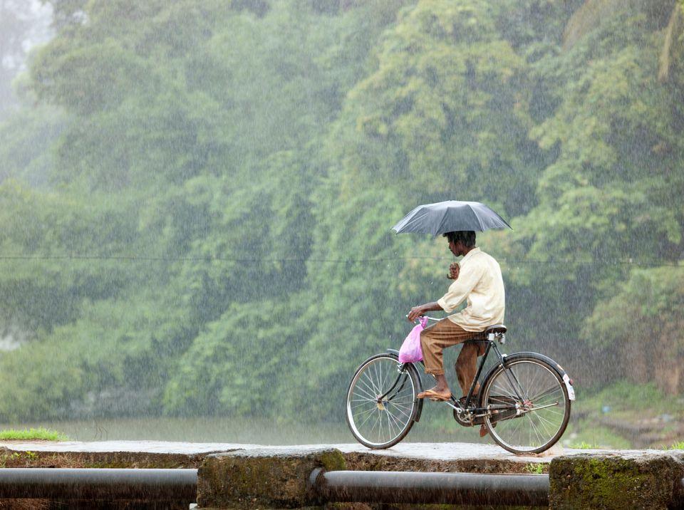 Man on bicycle traveling during monsoon season