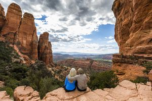 older couple sitting down and looking out at a red rock landscape in Arizona