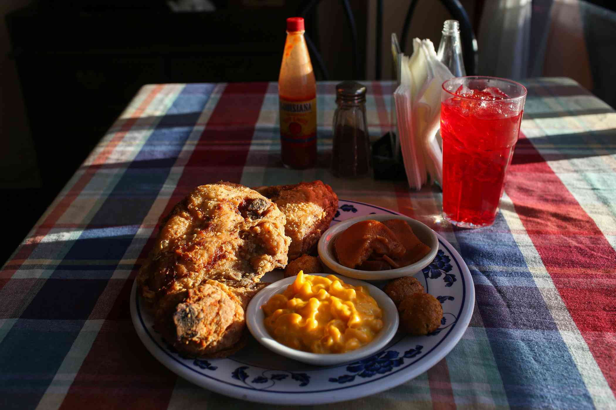A plate with fried chicken and sides with a red soda