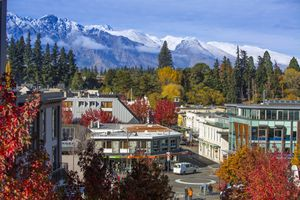 town scene with red autumn leaves in foreground and snowy mountains in background
