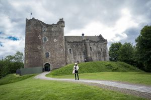 A tall woman wearing black leggings and a sweater stands ona brick sidewalk checking her smartphone on a summer day with a massive fortress behind her known as Doune Castle
