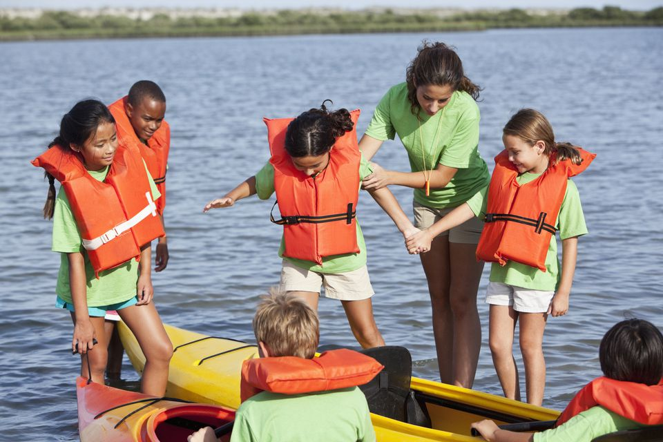 Summer camp counselor with children and kayaks