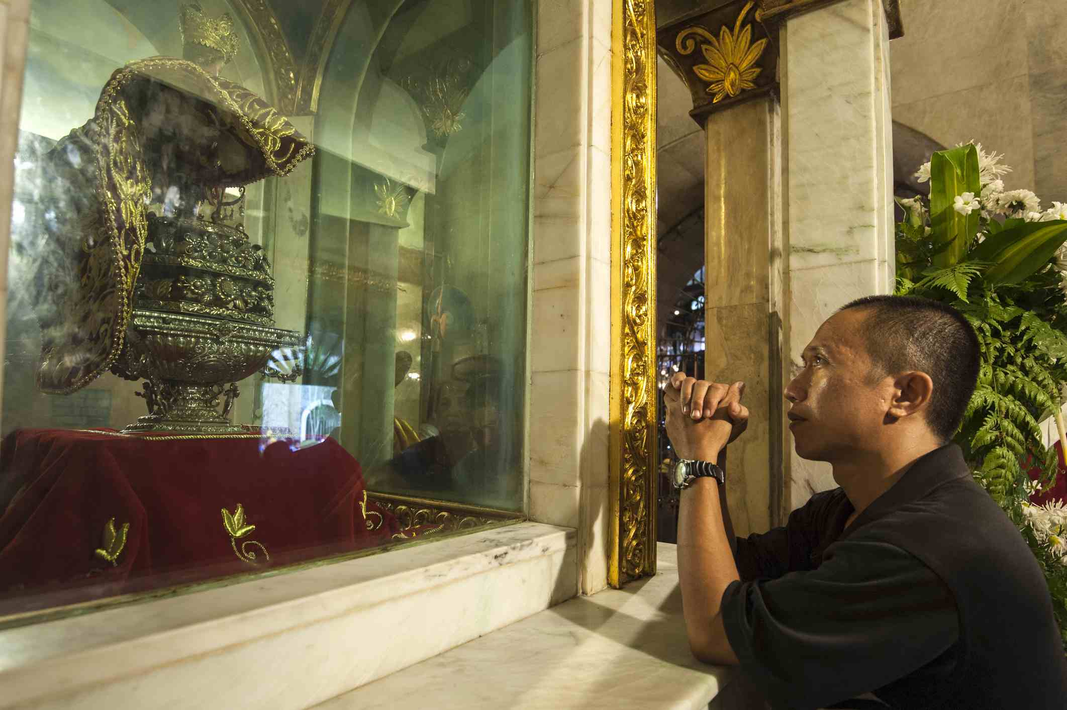 Filipino praying to Santo Nino in Cebu